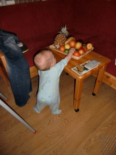 Amelie reser sig själv och står, griper efter frukt